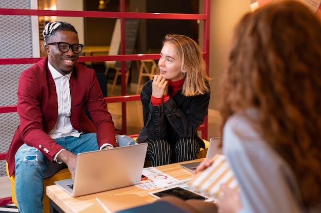 Heureux étudiant africain avec ordinateur portable parlant à l'une des filles tout en préparant ses devoirs ou en travaillant sur un projet ensemble