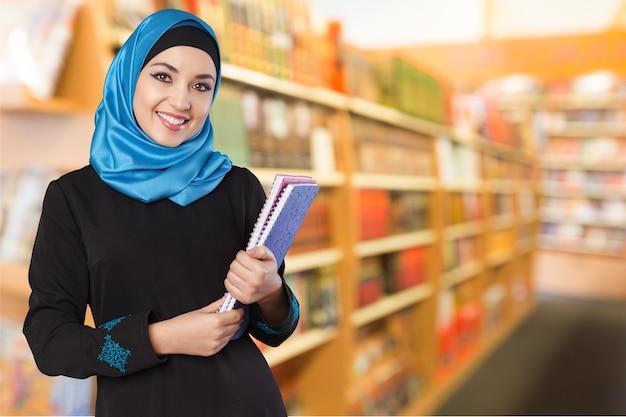 Heureux étudiant arabe saoudien tenant des dossiers isolés sur fond blanc
