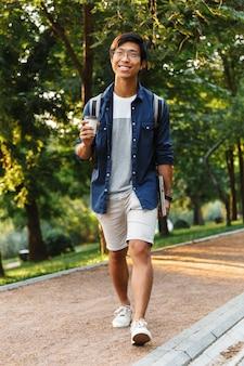Heureux étudiant asiatique à lunettes marchant avec ordinateur portable dans le parc