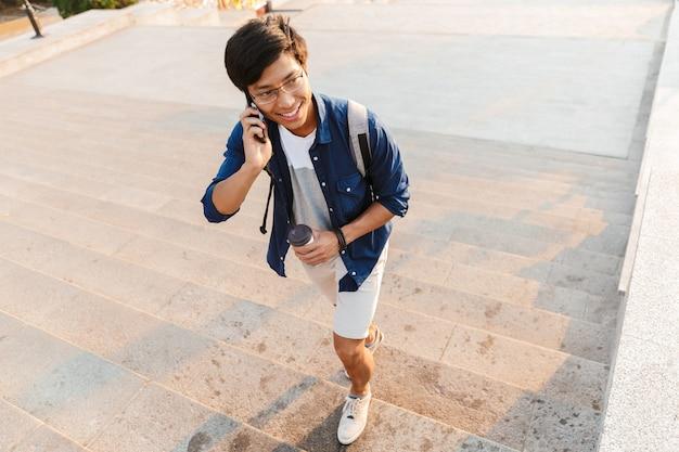 Heureux étudiant asiatique à lunettes parler par smartphone tout en regardant ailleurs et en marchant dans les escaliers à l'extérieur