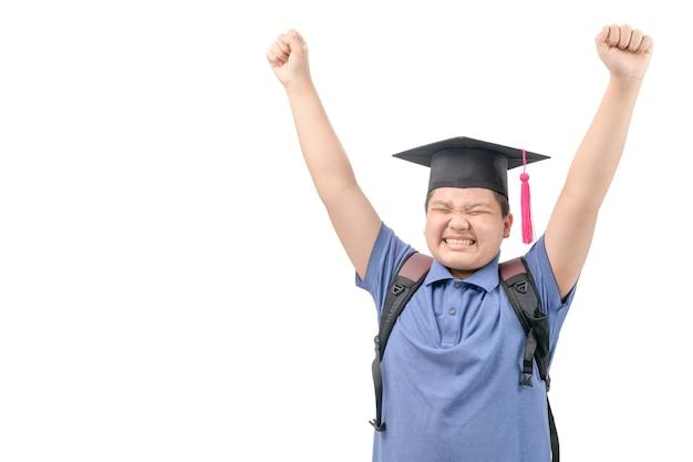 Heureux étudiant asiatique porter une casquette de graduation et levant la main isolé sur blanc