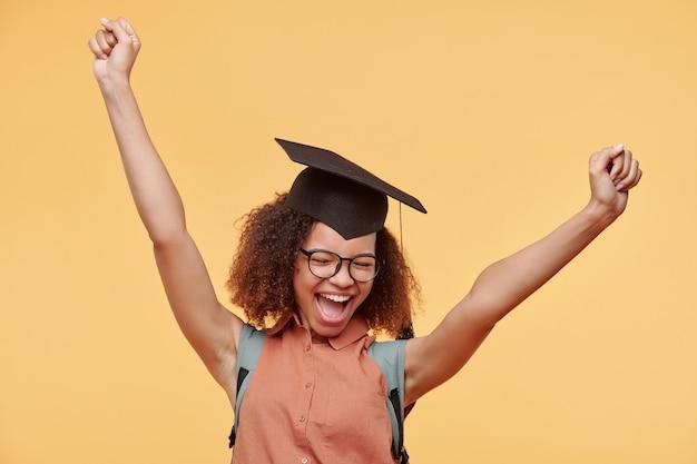Heureux étudiant diplômé noir excité en lunettes et bonnet académique levant les bras et criant après avoir terminé son diplôme