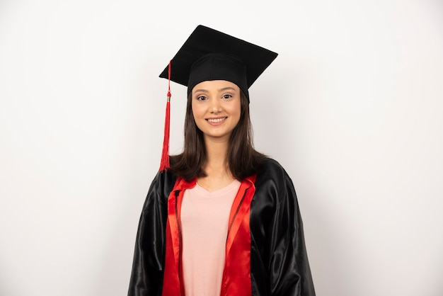 Heureux étudiant diplômé en robe debout sur fond blanc.