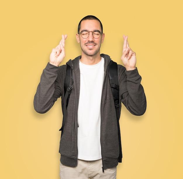 Heureux étudiant faisant un geste de doigts croisés