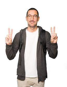 Heureux étudiant faisant un geste de victoire avec ses doigts