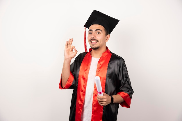 Heureux étudiant de sexe masculin avec diplôme faisant signe ok sur blanc.