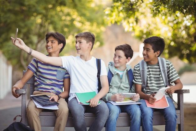 Heureux étudiants assis sur un banc et prenant selfie sur téléphone mobile