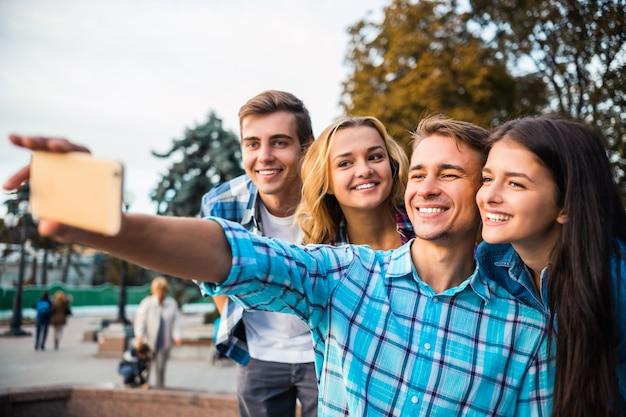 Heureux étudiants prenant selfie dans le parc ensemble