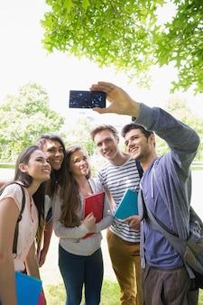 Heureux étudiants prenant un selfie à l'extérieur sur le campus de l'université