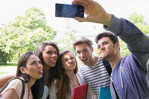 Heureux étudiants prenant un selfie à l'extérieur sur le campus