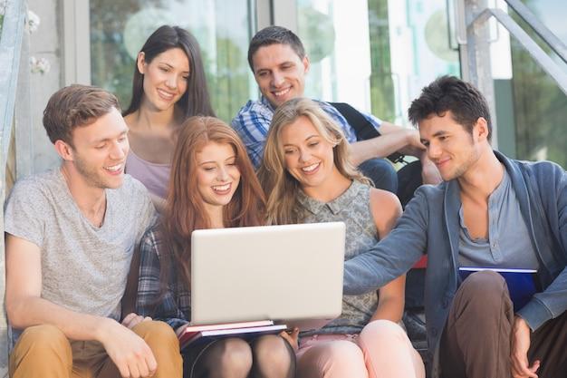 Heureux étudiants regardant un ordinateur portable à l'extérieur