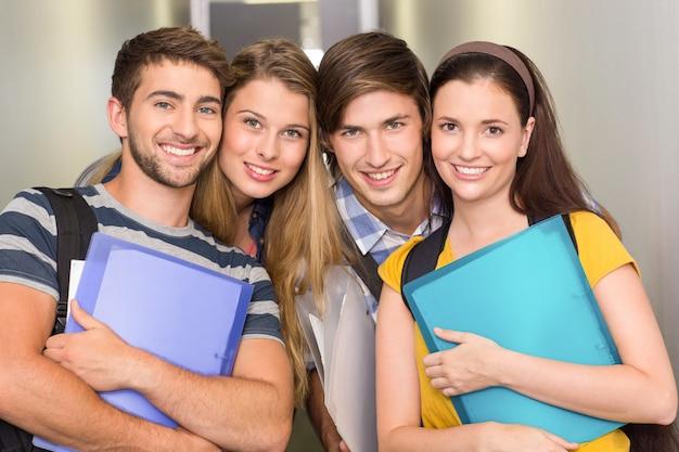 Heureux étudiants tenant des dossiers dans le couloir d'université