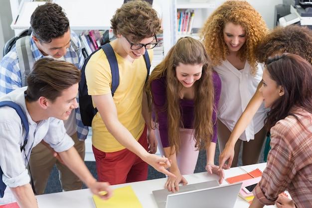 Heureux étudiants travaillant ensemble sur un ordinateur portable