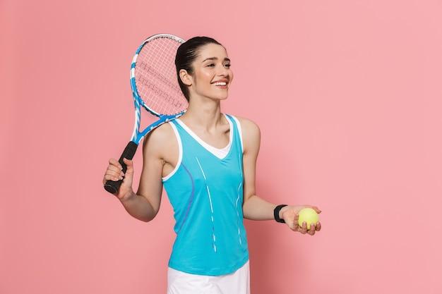 Heureux excité incroyable belle jeune jolie femme de remise en forme tenant une raquette de tennis posant isolé sur un mur rose
