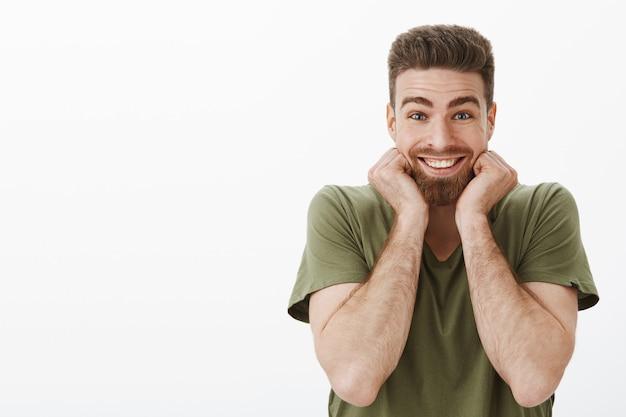Heureux, excité et ravi, beau mec barbu recevant un cadeau incroyable et agréable souriant de joie et d'étonnement touchant le visage surpris et étonné sur un mur blanc