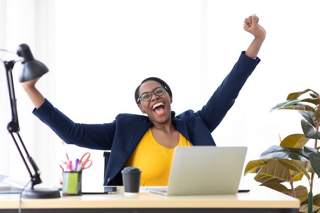 Heureux excité réussi belle femme d'affaires afro-américaine triomphant dans un bureau moderne avec ordinateur portable, pose heureuse de succès. travail à domicile