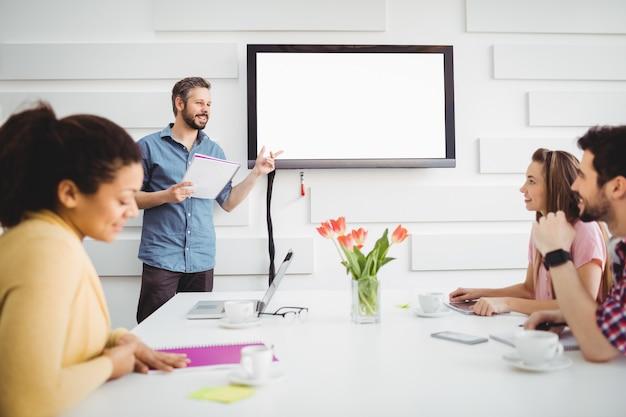 Heureux exécutif donnant la présentation aux collègues dans la salle de réunion au bureau créatif