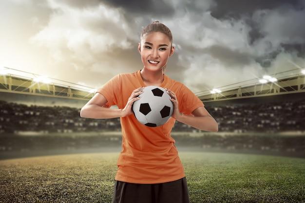 Heureux fan de football féminin tenant le ballon