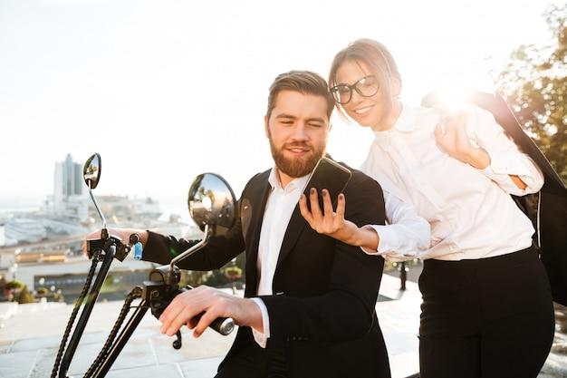 Heureux femme d'affaires debout près d'un homme barbu en costume