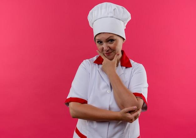 Heureux femme d'âge moyen cuisinier en uniforme de chef a mis sa main sur le menton sur un mur rose isolé avec copie espace