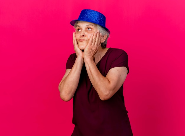 Heureux femme âgée portant chapeau de fête met les mains sur le visage à la recherche de rose