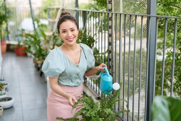 Heureux, femme asiatique, arrosage, plante, sur, les, balcon