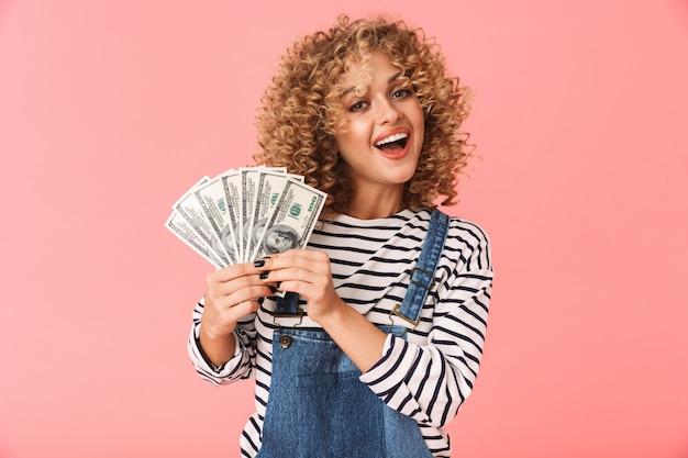 Heureux femme bouclée des années 20 tenant un ventilateur d'argent en dollars debout