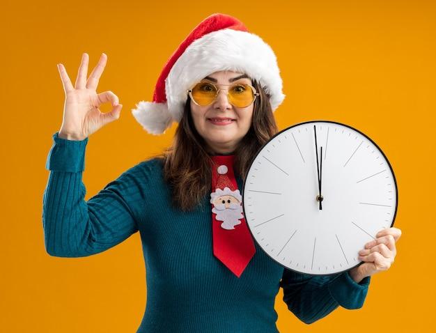 Heureux femme caucasienne adulte dans des lunettes de soleil avec bonnet de noel et cravate de santa tenant horloge et gesticulant signe ok isolé sur fond orange avec espace copie