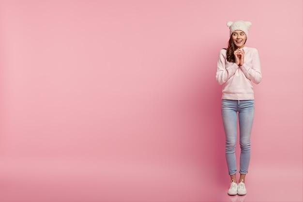 Heureux femme heureuse garde les mains jointes, regarde de côté avec l'intention de faire quelque chose, porte un chapeau blanc avec des oreilles