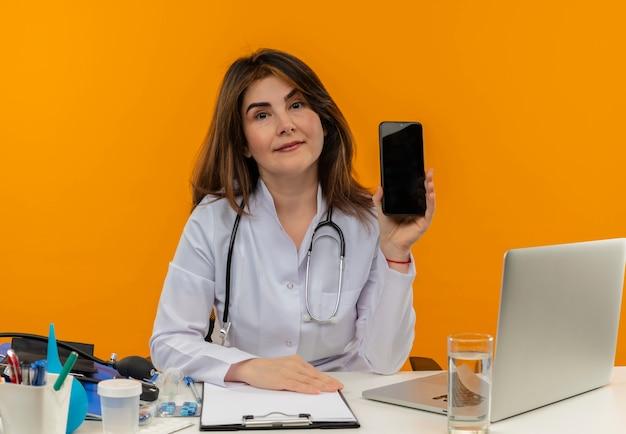 Heureux femme médecin d'âge moyen portant une robe médicale avec stéthoscope assis au bureau de travail sur un ordinateur portable avec des outils médicaux tenant le téléphone sur un mur orange isolé avec espace de copie