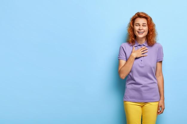 Heureux femme millénaire aux cheveux roux ondulés posant contre le mur bleu