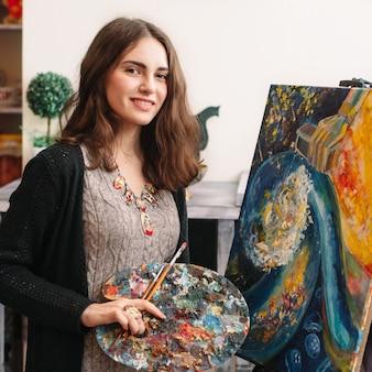 Heureux femme peintre en studio d'art avec photo