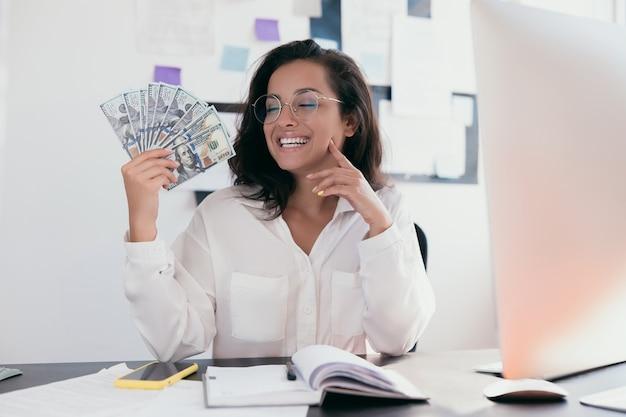 Heureux femme portant des vêtements de bureau chemise blanche et lunettes rondes tenant un ventilateur d'argent et assis au bureau