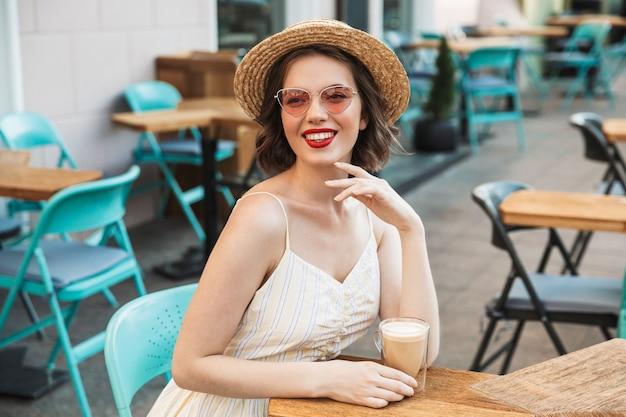 Heureux femme en robe et chapeau de paille se reposer
