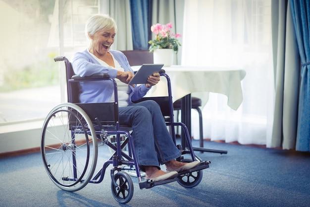 Heureux femme senior en fauteuil roulant à l'aide de tablette numérique