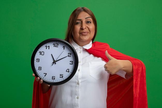 Heureux femme de super-héros d'âge moyen tenant horloge murale montrant le pouce vers le haut isolé sur vert