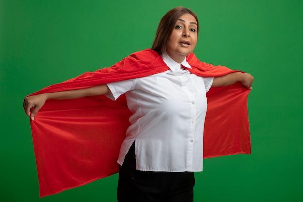 Heureux femme de super-héros d'âge moyen tenant manteau isolé sur fond vert