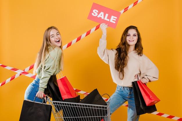 Heureux femmes souriantes ont signe de vente avec panier rempli de sacs à provisions et de ruban de signalisation isolé sur jaune