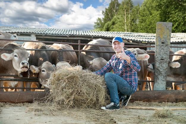 Heureux fermier mâle mains montrant les pouces vers le haut dans la ferme de vache