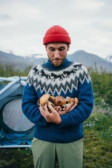 Heureux, fier homme cueilleur en pull traditionnel en laine bleue avec des ornements se dresse sur un terrain de camping dans les montagnes, tient dans les bras tas de champignons délicieux et biologiques