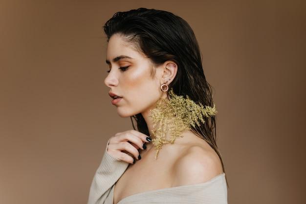 Heureux fille caucasienne regardant vers le bas. femme triste aux cheveux noirs posant avec plante.