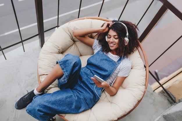 Heureux fille noire portant des chaussures de sport à la mode se détendre sur une chaise sur un balcon, profiter du matin seul