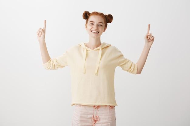 Heureux fille rousse souriante pointant les doigts vers le haut