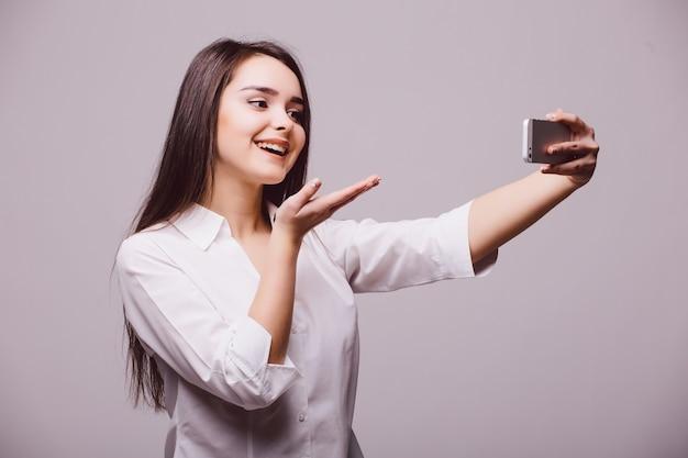 Heureux flirt jeune femme à prendre des photos d'elle-même au téléphone intelligent soufflant un baiser, sur fond blanc