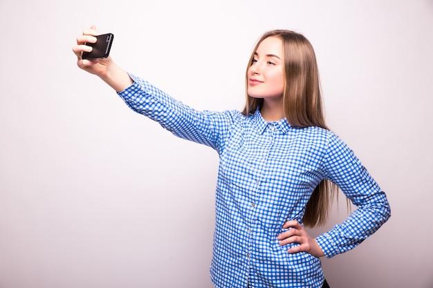 Heureux flirt jeune fille à prendre des photos d'elle-même au téléphone intelligent, sur un mur blanc