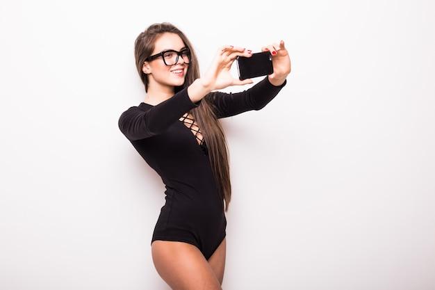 Heureux flirt jeune fille à prendre des photos d'elle-même à travers un téléphone portable, sur un mur blanc