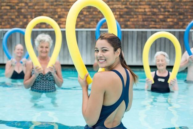 Heureux formateur aidant les nageurs seniors avec des nouilles de piscine