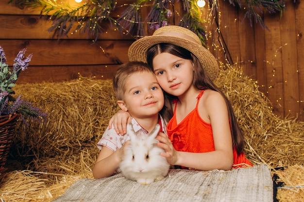 Heureux frère et soeur embrassent un lapin dans le village sur le foin