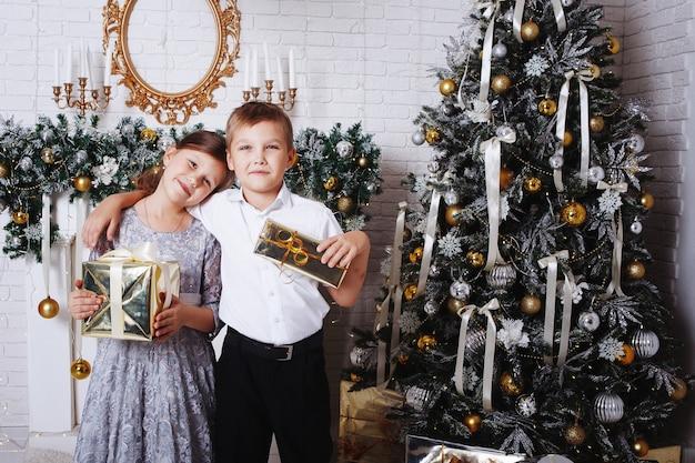 Heureux frère et soeur près de l'arbre de noël avec des cadeaux de noël