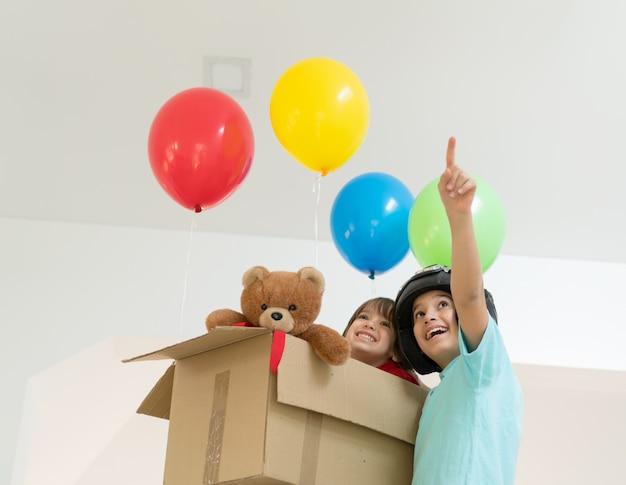 Heureux frères jouant avec des ballons et boîte de carton